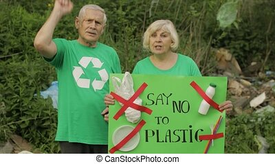 Senior old activist team holding protesting poster Say No To Plastic. Calls out slogans around bags bottles in forest. Save environment ecology stop cellophane nature pollution. Recycle garbage