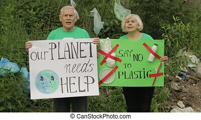 Senior old volunteer activist team holding protesting posters Our Planet Needs Help, Say No To Plastic. Calls out slogans around bags bottles in park. Reduce trash nature pollution. Recycle rubbish