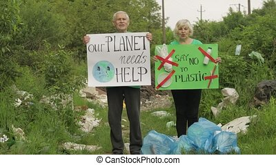 Senior volunteers with protesting posters Our Planet Needs ...