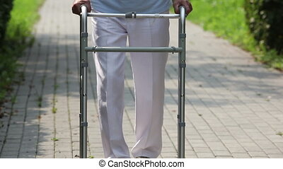 Senior walker - Close-up of a retired man using a walker...