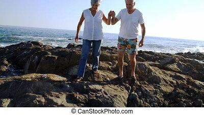 Senior walking on rock 4k - Senior walking on rock on a...