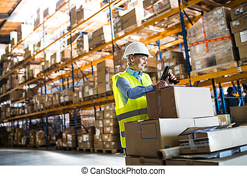Senior warehouse woman worker working with barcode scanner.