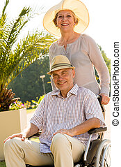 Senior wife with husband in wheelchair - Happy senior wife...