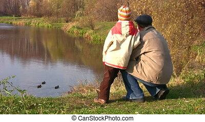 senior with child. Ducks on pond.