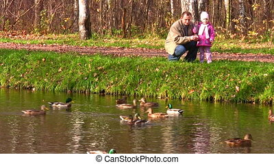 senior with child near pond with ducks