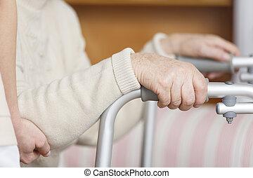 Senior with hands on walker