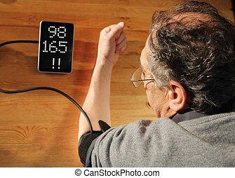 Senior with hypertension measuring blood pressure