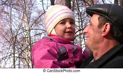 senior with little girl faces in autumn park
