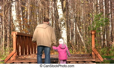 senior with little girl in autumn park on bridge