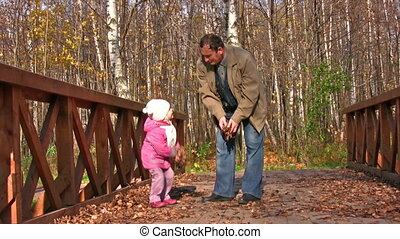 senior with little girl in autumn park on bridge throw leaves