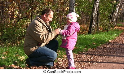 senior with little girl in autumn park with mitten
