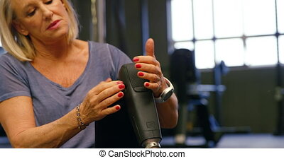 Senior woman adjusting her prosthetic leg 4k - Senior woman...