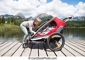 Senior woman and children in jogging stroller, summer day. -...