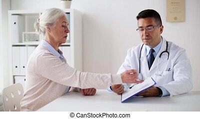 senior woman and doctor with cardiogram at clinic -...