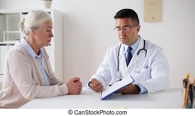 senior woman and doctor with cardogram at hospital -...