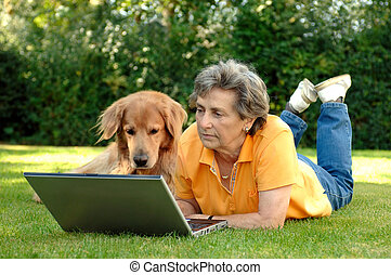 Senior woman and dog with laptop