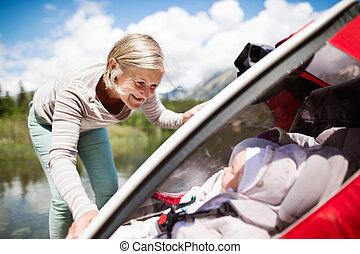Senior woman and grandchildren in jogging stroller. - Senior...