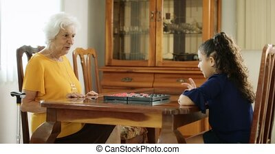 Senior Woman And Little Girl Playing Checkers Board Game