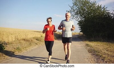 Senior woman and man running or jogging on a field to remain...
