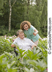 Senior woman and nurse in a garden - Senior woman sitting on...
