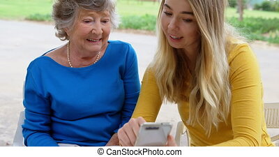 Senior woman and young girl discussing on mobile phone 4k -...