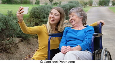 Senior woman and young girl taking selfie 4k - Smiling...
