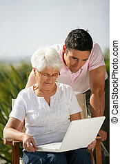 Senior woman and young man watching a laptop