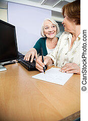 senior woman, användande dator, medan, klasskamrat, skrift antecknar