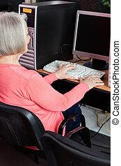 senior woman, användande dator, på skrivbordet, in, klassrum