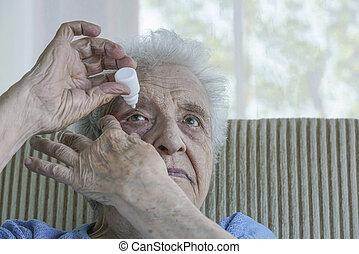 senior woman applying eye drop on her eye