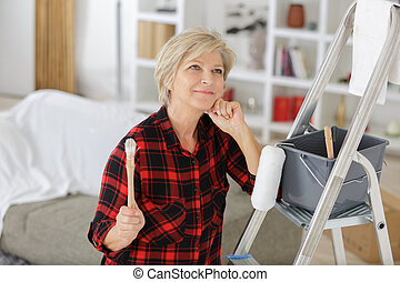 senior woman as a painter in front of white background