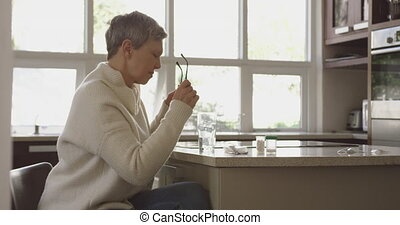 Senior woman at home alone - Side view of a senior Caucasian...