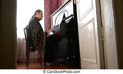 Senior woman at home is playing the piano