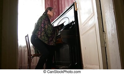 Senior woman at home is starting plays the piano