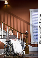 Senior woman at home sitting in wheelchair