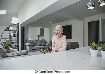 Senior Woman At Home - Happy senior woman is smiling for the...
