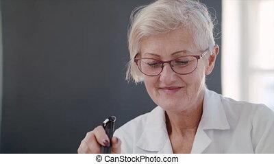 Senior woman at repair cafe, looking at camera.