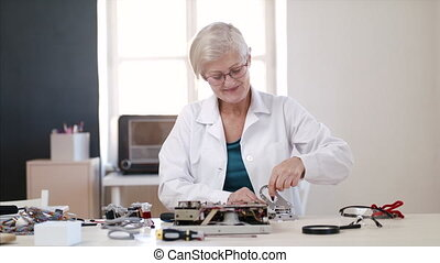 Senior woman at repair cafe repairing household electrical devices.