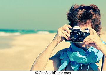 senior woman at the beach with old vintage camera