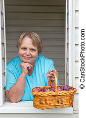 Senior woman at window with basket