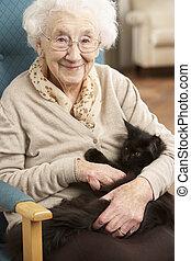 senior woman, avkopplande, i stol, hemma, med, husdjuret,...