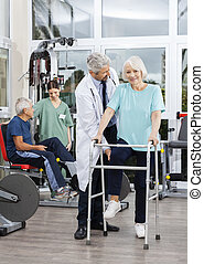 Senior Woman Being Assisted By Doctor At Rehab Center -...