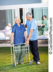 Senior Woman Being Assisted By Male Caretaker