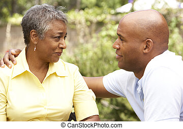 Senior Woman Being Consoled By Adult Son