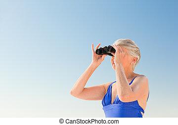 Senior woman bird watching at the beach
