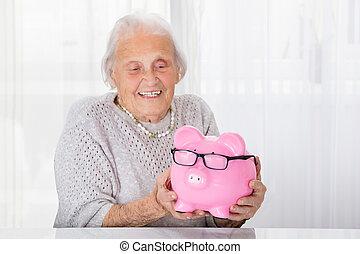 senior woman, birtok, piggybank