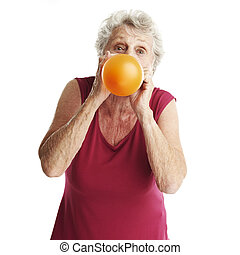 senior woman blowing balloon - portrait of senior woman...