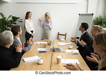 Senior woman boss introducing new worker, team welcoming at meet