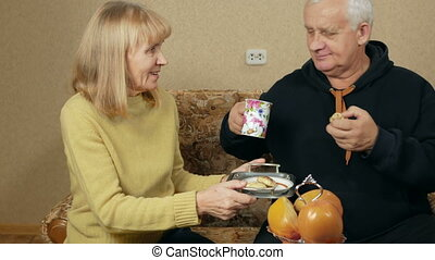 Senior woman brings a man to a tray of tea and biscuits. They choose a TV program and relaxing together at home on the couch.