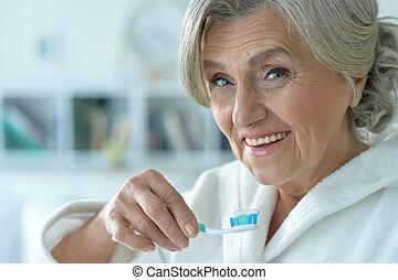 Senior woman brushing her teeth - Portrait of happy senior...